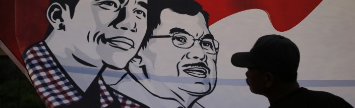 A worker pulls down a poster of Indonesia's presidential candidate Joko Widodo and his running mate Yusuf Kalla after a campaign rally in Cirebon