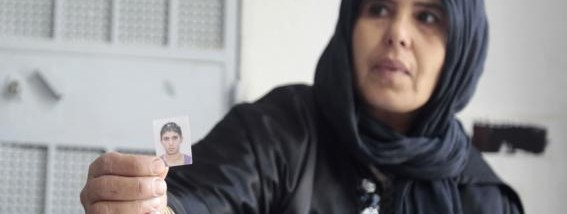 The mother of Bilel Kaabi, who died while fighting in the ranks of extremists in Iraq and Syria, shows a photo of her son during an interview with Reuters in the rural town of Oueslatia